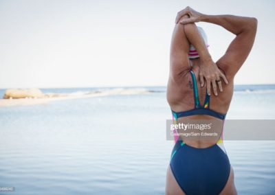 Female open water swimmer stretching arm and shoulder in ocean surf